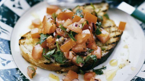 Blanda tomater och lök med citronsaft och olivolja. Smaka av med salt, en nypa socker och svartpeppar. Grovhacka koriandern och vänd ner. Pensla brödskivorna med lite olivolja och grilla. Fördela tomatsalladen på skivorna.
