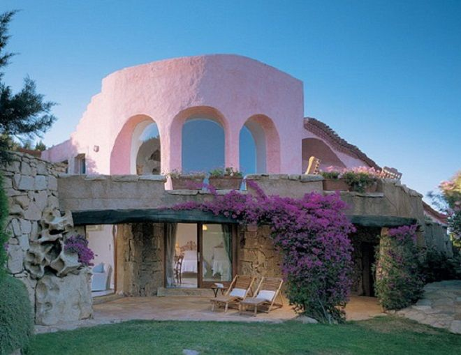 "Sardinia's Costa Smeralda. The house was built in the 1960s by architect Savin Couëlle. ""The heart of the house,"" Couëlle says is the twenty-foot-high living room, with its off-center vaulted ceiling and three large arched windows. A recent owner has painted the house pink. architecturaldigest.com"
