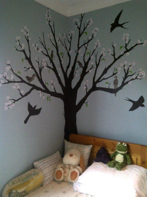 Child's room blossoming tree painted in corner of room. Every first day of Spring we add more leaves.