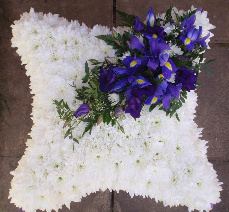 cushion tribute with purple spray, and ribbon edge for gentleman.