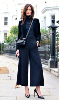 Mulher morena posa para foto na calçada de Londres usando turtleneck preta com blazer de veludo preto por cima, calça pantalona cropped, scarpin preto e bolsa a tiracolo na transversal