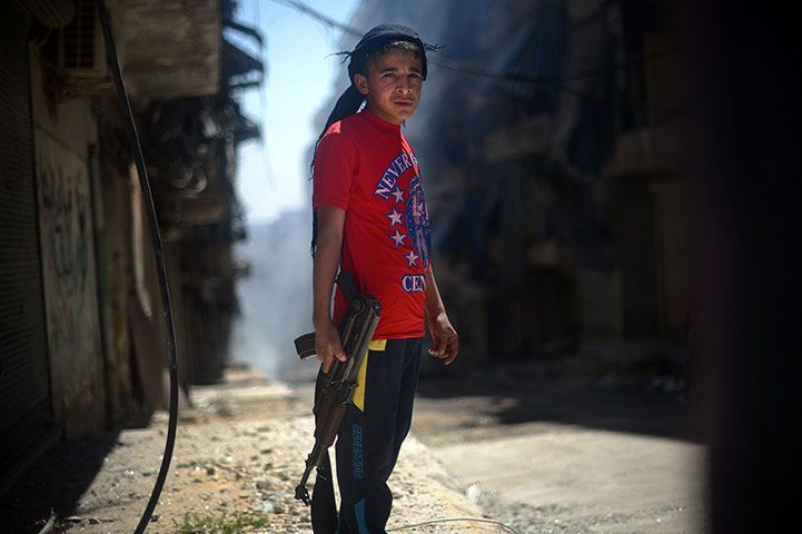 Photographer Dimitar Dilkoff continued his excellent work in Syria. Here, a Syrian boy holds an AK-47 assault rifle in Aleppo