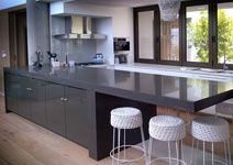 Samsung Radianz Ural Grey Kitchen Island with 100mm mitre edge and leg. The rest if the kitchen was done in pure white to give a contrast. The island  was reinforced with a steel structure to support the weight of the overhang. Manufactured and installed by Rock  Stone. Location De Kelders, Gansbaai.