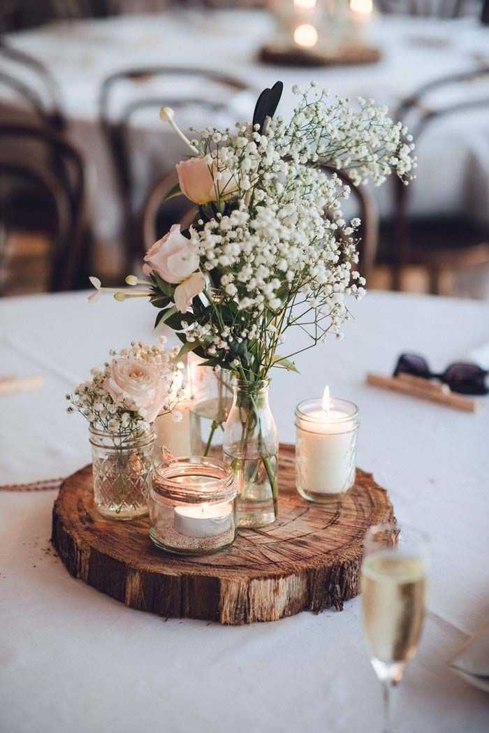 A Relaxed Garden Soiree Wedding In Kiama. A mixture of flowers and candles delicately arranged on a tree trunk as a wedding table decoration.