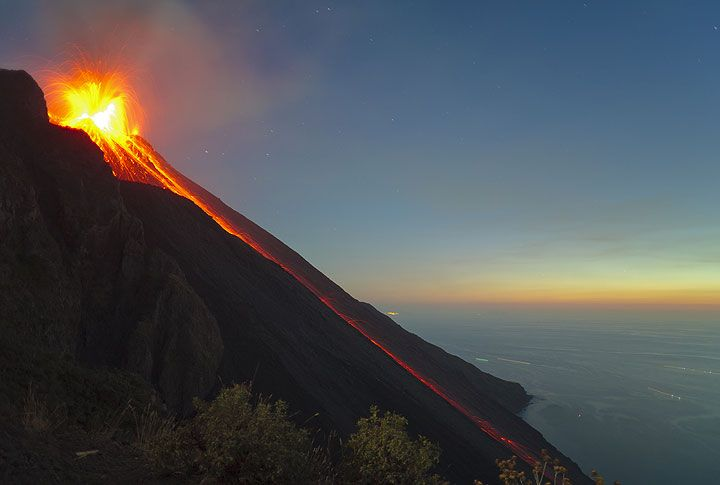 A very powerful eruption showers the whole crater with bombs, and probably reaches the Pizzo as well. The heavy bombardment results in glowing rockfalls lasting for more than a minute on the Sciara del Fuoco, with many bombs reaching the sea. (Photo: Tom Pfeiffer)