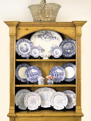 Plates All Symmetrical: Here, an arrangement of blue-and-white plates and platters gains interest from a range of blue tones and a variety of sizes, framed in a vintage-look pine cupboard.