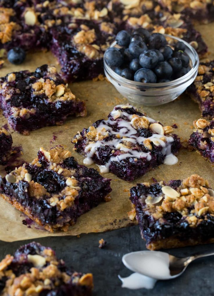 A pan of blueberry crumble bars on parchment paper with a bowl of blueberries in the background.