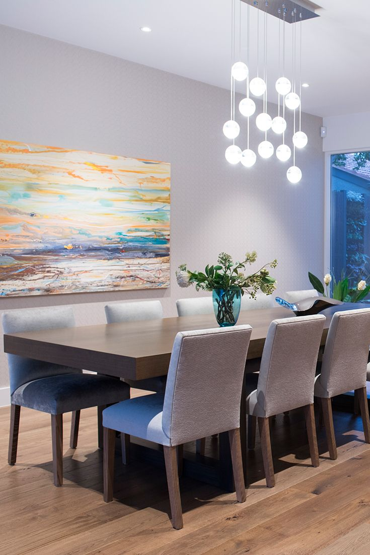 Dining space featuring pendant lighting and custom made dining chairs and table with additional decorative elements such as the geometric wallpaper.