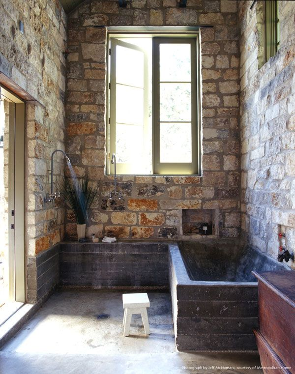 more primitive modern - stone walls and concrete tub; french casement windows and a sweet little stool; by mell lawrence