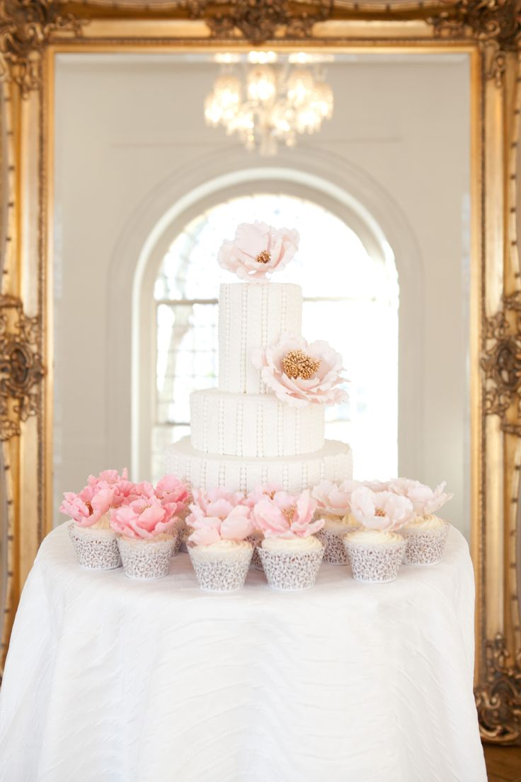 White pearl cake with pink ombre cupcakes in front of a large gold mirror for a Marie Antoinette shoot featured on Wedluxe.