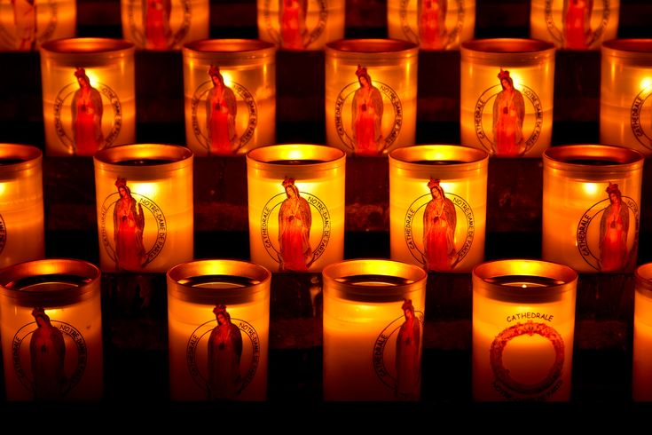 A close up view of candles, featuring the Virgin Mary, inside the Notre Dame Cathedral in Paris, France
