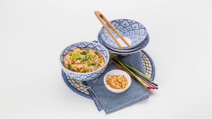 Beroemd in Thailand: het bordje gebakken noedels met een eitje erdoor en pinda's en limoen erover. Wij maken pad thai met kipfilet. RijstnoedelsDoe 220 gram rice noodles in een ruime kom en schenk er 2 liter kokend water op tot ze helemaal onderstaan. Dek af met vershoudfolie, laat 10 minuten staan en giet af. Roerbak-eitjePers ondertussen 1 limoen uit en meng het sap met 4 eetlepels ketchup, 4 eetlepels vissaus en 2 eetlepels donkere basterdsuiker. Snijd 300 gram kipfilethaasjes in stukjes…