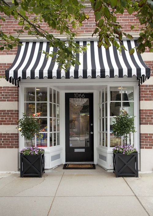 Black & white striped awning on a stunning little storefront.