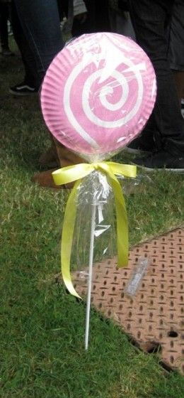 To make these lollipops, buy 2 or 3 ft wooden dowels from a hardware store and then use hot glue to attach two paper plates to the stick to form a 3D lollipop shape. Paint and apply glitter and then finish with sheets of plastic (or plastic wrap) tied with ribbons.