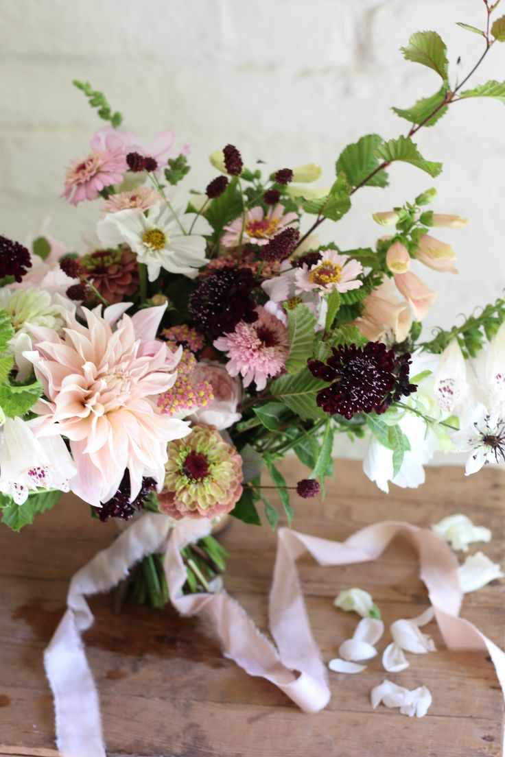British grown summer flowers wedding bouquet by Jennifer Pinder - a florist based in Kent. Pink and peach flowers with touches of burgundy and a silk ribbon by Kate Cullen. The flowers are all British grown and include zinnia, cafe au lait dahlias, foxgloves, scabious and cosmos. A beautiful late summer bouquet.
