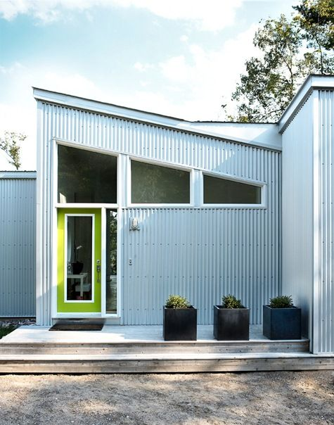 Corrugated steel siding installed in juxtaposition to the sloping roofline wrap around similarly angled windows.  The silver of the steel is broken up delightfully by a chartreuse bordered door with glass insert.  Clean lined planters on the seasoned deck balance the look.