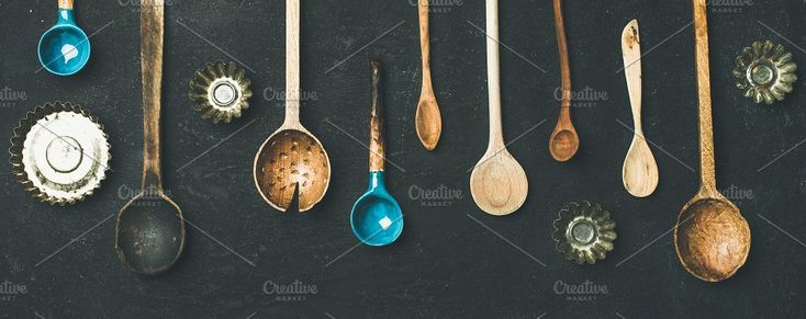 #Various vintage kitchen spoons  Flat-lay of various old vintage kitchen spoons and baking tin molds over black stone background top view copy space wide composition. Rustic cooking concept