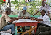"""""""Many know the sport of Barbados is cricket, but do you know what the game played most in Barbados is? One can be very sure that you can find and any time during the day or night a game of DOMINOES being played. Whether in a rum shop, lunchroom, at a picnic or a local lime under the tree you will find a gathering of people sometimes very quiet in concentration or sometimes very animated and theatrical as they slam dominoes onto a board."""""""