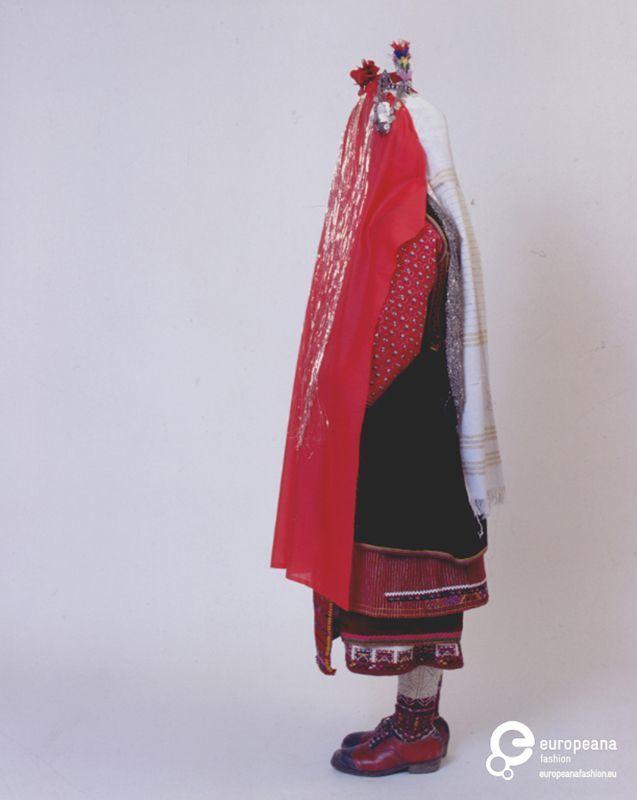 """Ανω Ορεινή Σερρών: η νύφη είναι καλυμμένη με την """"τσίπα"""" (κόκκινο μαντίλι) και τα """"τέλια"""" (χρυσές κλωστές). Ημερομηνία: Late 19th c.   Ημερομηνία δημιουργίας: 1800/1899  Συλλέκτης: Peloponnesian Folklore Foundation   Ίδρυμα: Europeana Fashion"""