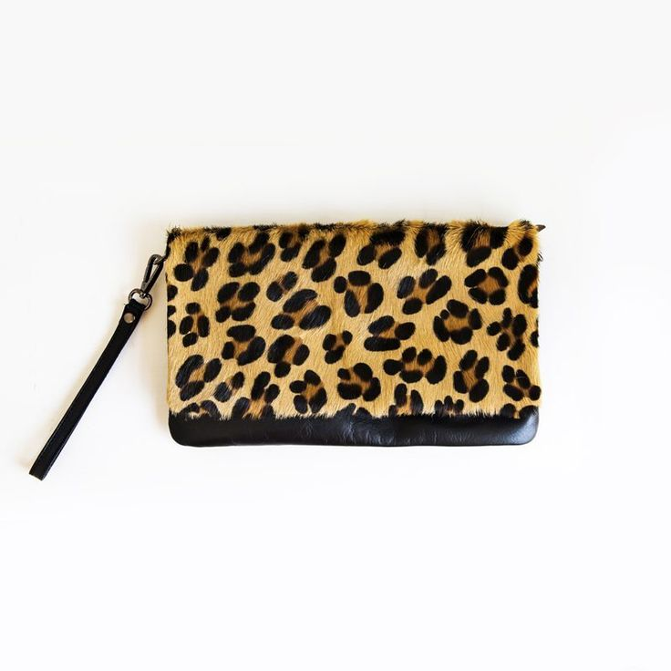 Animal print leather clutch bag with detachable wrist strap and long handbag strap. Italian leather with a leopard print, hair hide flap. Large enough to fit all the essentials. Lined with an inner zip pocket and with a zip closure and a magnetic popper. Fab addition to an evening outfit or easy to throw on with jeans using the cross-body strap. 28cm x 17cm.