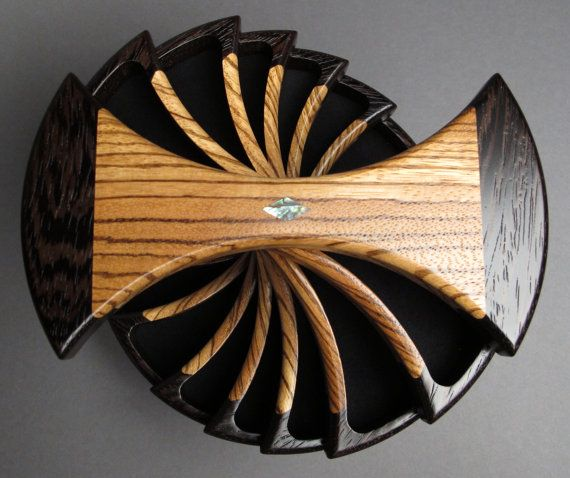 This Zebrawood jewelry box named The Helical box is a unique symmetrical design that pivots around a brass rod. The 14 compartments are lined with