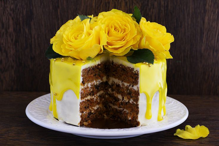 Homemade carrot cake decorated with yellow roses and glaze.