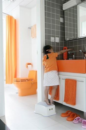 Child Reaches Up To Sink In Bright Orange Bathroom Grey Interior Paint Orange Bathroom Paint