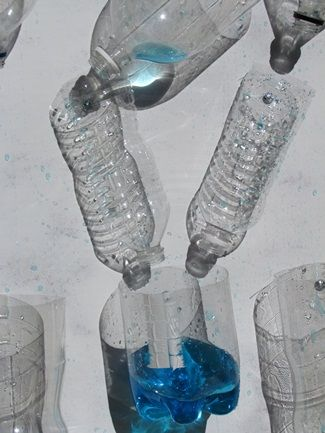 This is made with cardboard--I made one with white peg board from home depot and it works great! I put an extra long/large tub at the bottom to recycle the water. Use flat bolts with nuts to attach the plastic bottles, funnels, jugs, whatever...