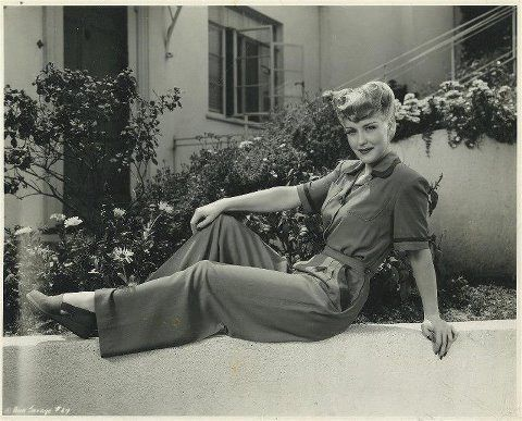1940s | girl lounging on wall in shirt + pants | vintage 40s style | casual day fashion style