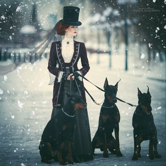 Victorian Woman with Dogs in the Snow (From 'Walking in a Winter Wonderland') - For costume tutorials, clothing guide, fashion inspiration photo gallery, calendar of Steampunk events, & more, visit SteampunkFashionGuide.com