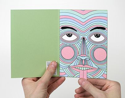 Annual personal holiday card which consists of a pink envelope with a die cut face, which opens to reveal a green card. The card opens to reveal a colorful face with tongue sticking out that functioned as a pull tab. When the tongue is pulled, the charact…