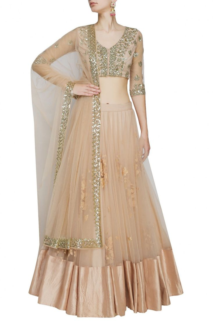 This set features a peach lehenga in net base appliqued with cream thread floral embroidery all over the front and back and criss cross sequins border around the hem. It has a can-can underlayer. It c