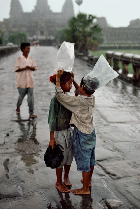 steve mccurry(1950- ), cambodia. angkor wat. 1998. children cover their heads with plastic bags in the rain.
