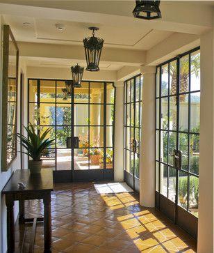 Mediterranean-style entry hall in Santa Barbara, bronze doors by Riviera Bronze Mfg.