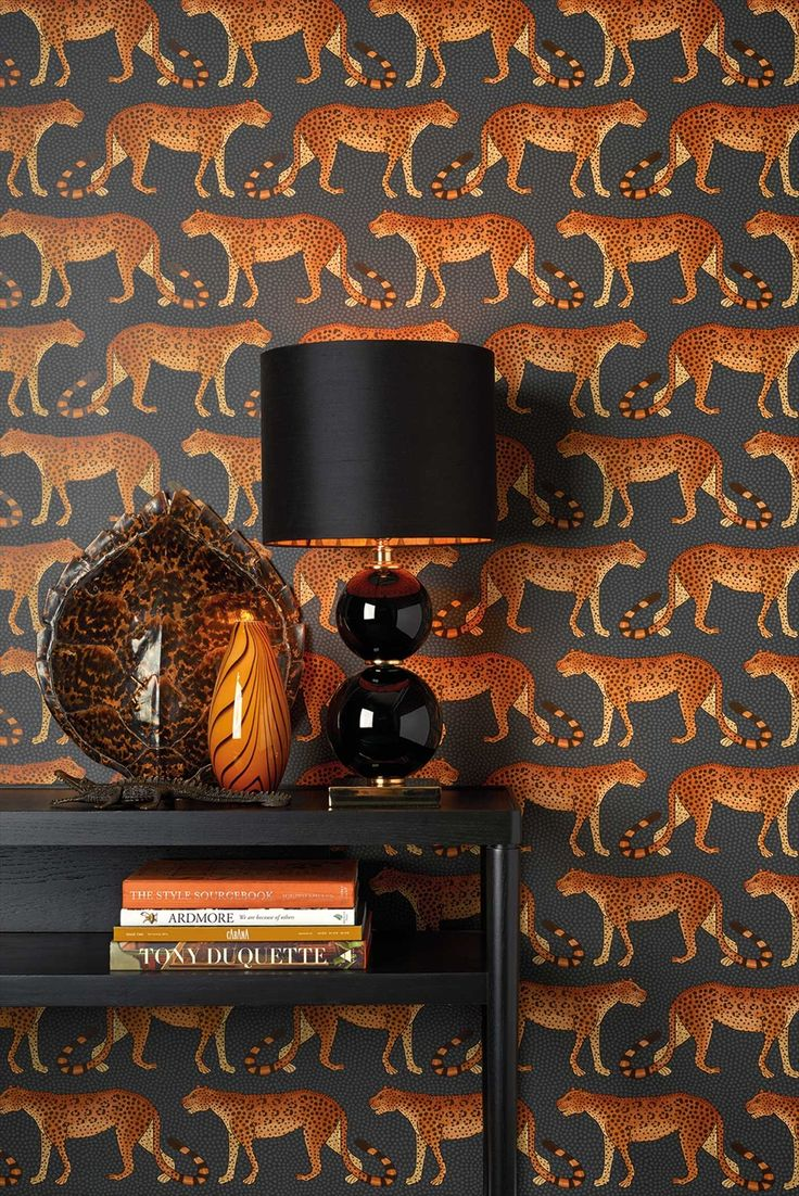 #ColeAndSonWallpaper Leopards march left and right across this wallpaper, their tails forming patterns and rythms associated with Zulu dance and music. Originally painted by Punch Shabalala, one of Ardmore's oldest and most esteemed artists, Leopard Walk is a simple yet striking design offered in five colourings including soft greys and taupes, a striking balck and white and a rich and moody charcoal with burnt orange, almost fire-lit leopards.Leopard Walk 109-2008 by Cole & Son wallpaper