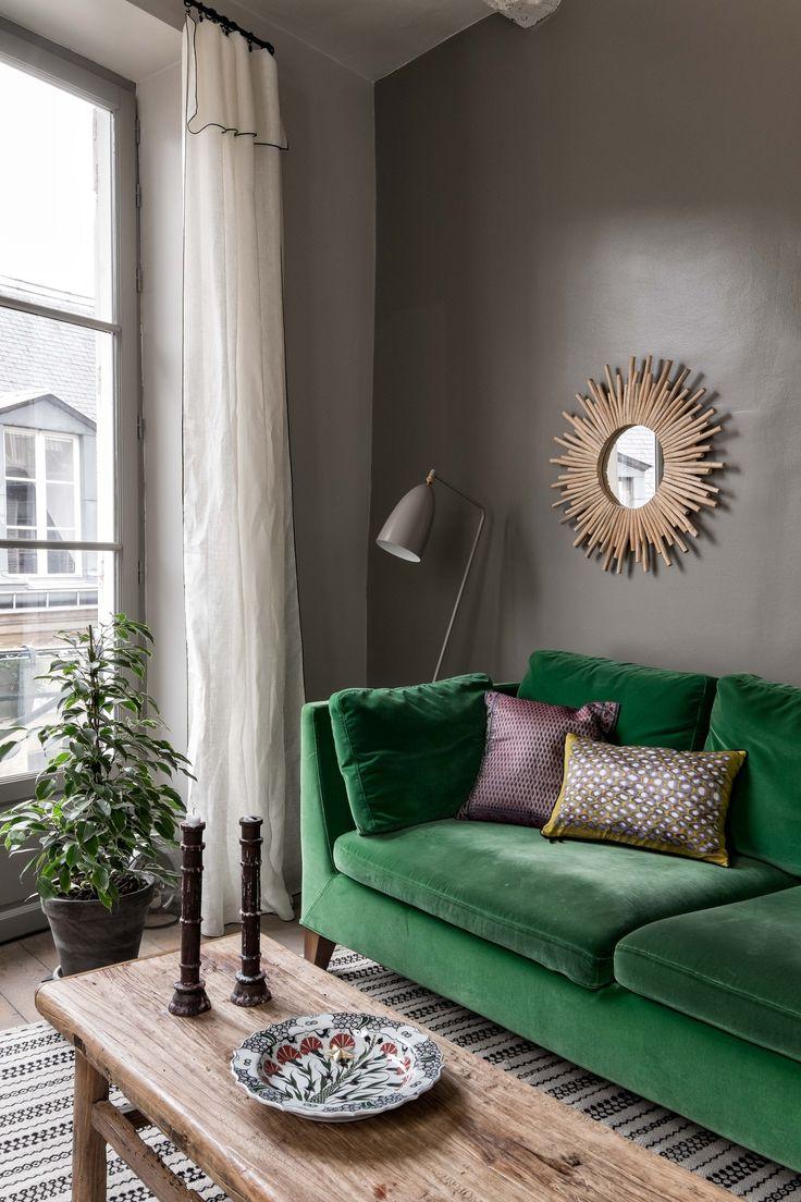 a velvet green sofa before a dark wall