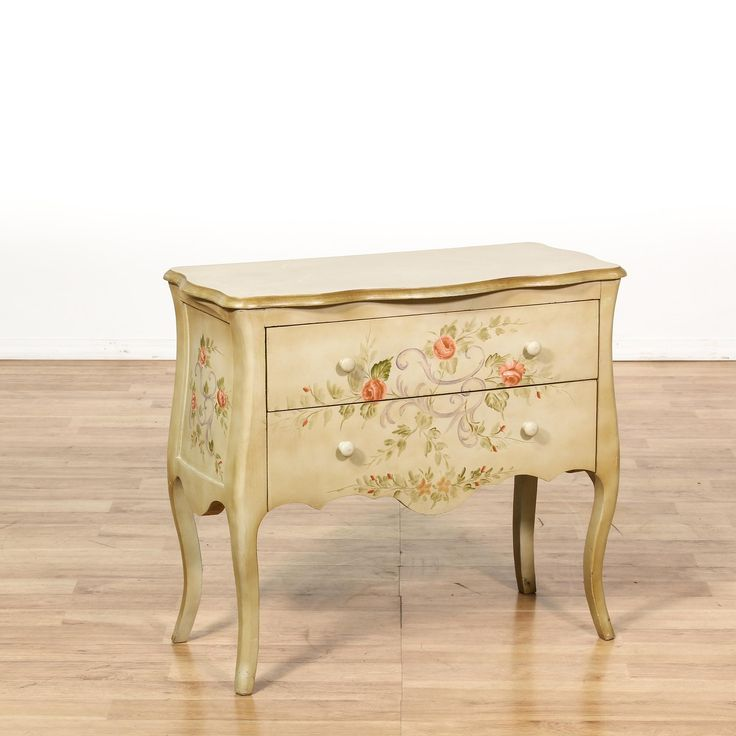 This cottage chic dresser end table is featured in a solid wood with a light beige finish. This chest of drawers has curved trim, 2 drawers and floral painted accents. Adorable side table perfect as a large nightstand! #shabbychic #dressers #shortdresser #sandiegovintage #vintagefurniture