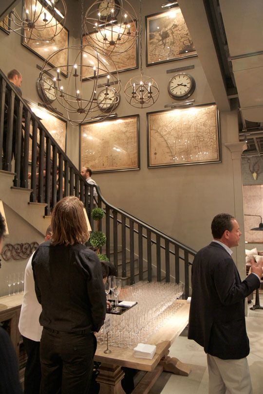 this was originally pinned for the chandeliers but I am enthralled with the wall features.  Love the clock and map installation. Great use of height and scale