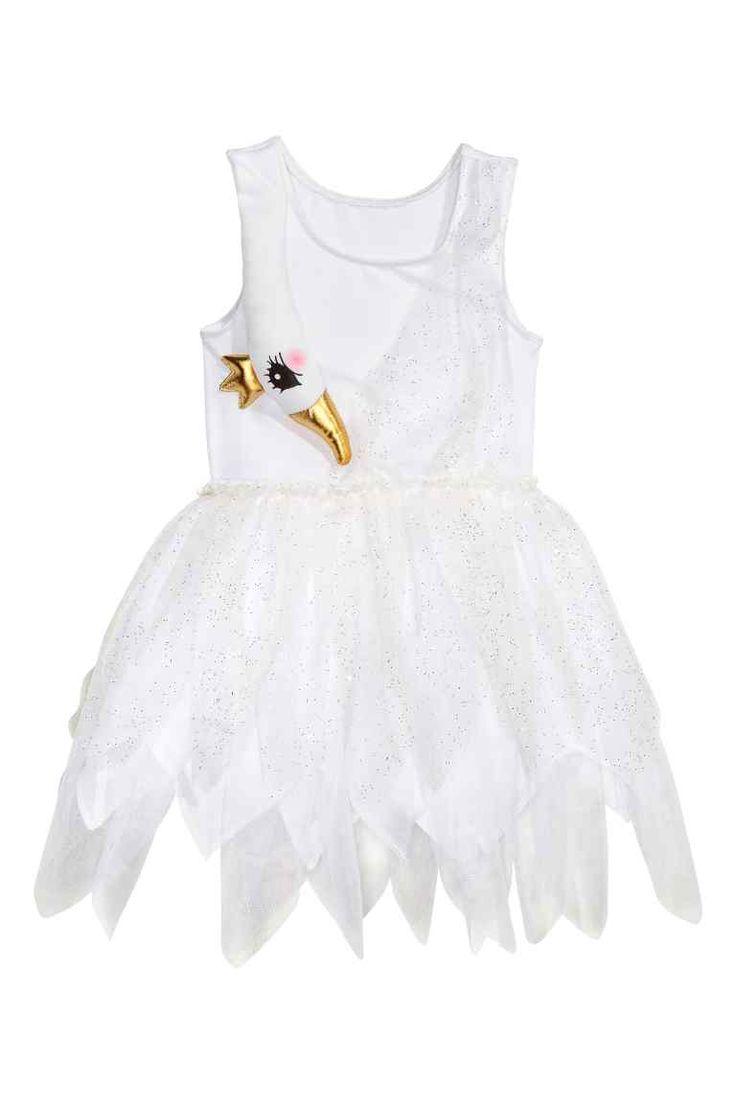 Zwanenjurk: Een mouwloze verkleedjurk met een gewatteerde applicatie in de vorm van een zwaan vooraan. De jurk heeft elastiek in de taille, een uitlopende rok met een puntige snit aan de onderkant en een laag glittertule erover. De rok is gevoerd.