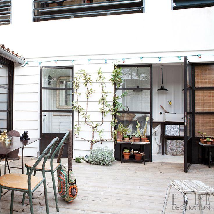 Questo cortile centrale rivestito - il cuore di questa bella casa in Francia Île de Ré - conduce nella lavanderia, dove un semplice scaffale aperto e pulito e scatole di immagazzinaggio a motivi geometrici creano un angolo ripostiglio.