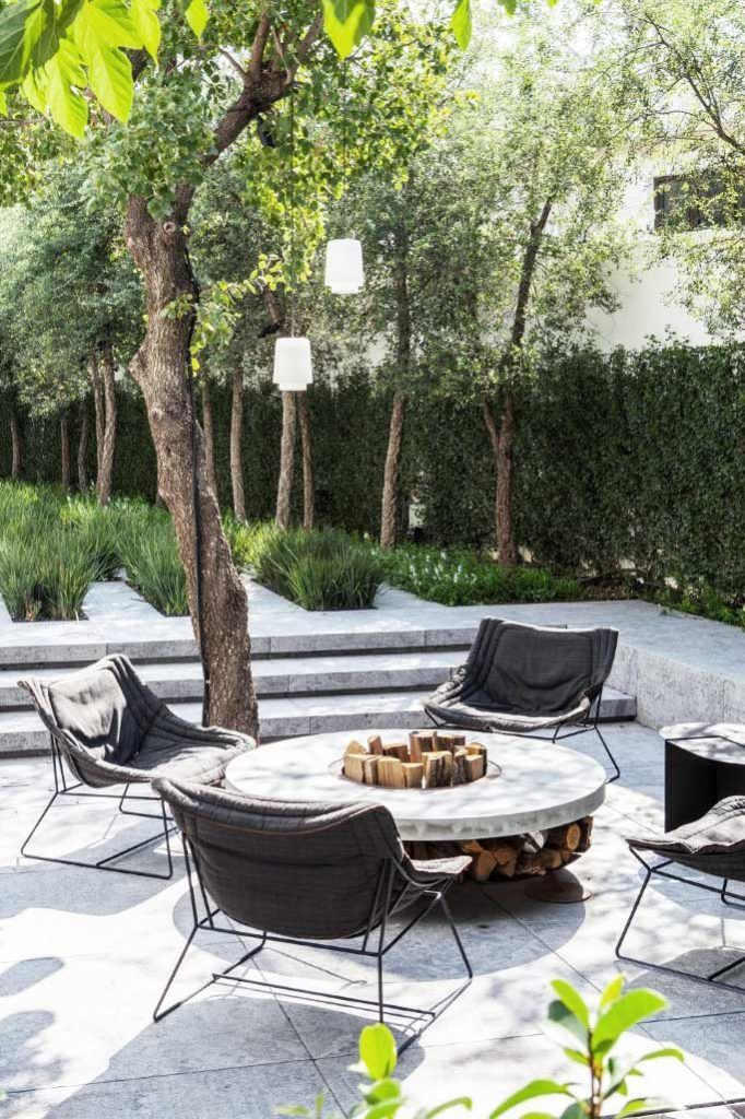 Patio with modern lounge chairs around fire pit on Thou Swell @thouswellblog