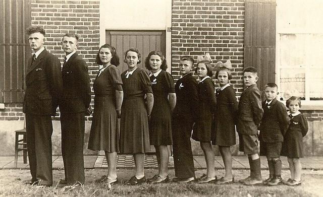 Kinderrijk gezin uit Oploo, waarvan de jongste dochter in 2010, 72 jaar is en de oudste zoon 87 jaar geworden zou zijn.  Watermolenstraat  Oploo, 1935. Naam Fotograaf: Onbekend  Fotonummer: DCWES-000006