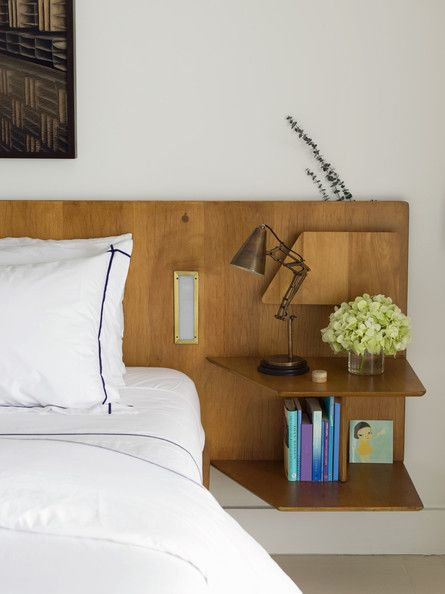 We call it the anti-bedside table: shelves! Here, they're brilliantly built into a gorgeous custom headboard.