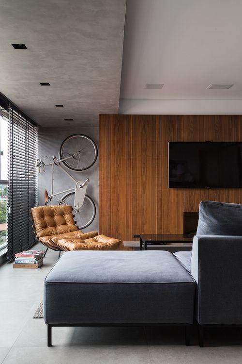 Sala de estar, sofá cinza, painel de madeira como suporte de televisão.