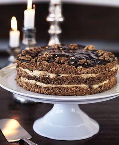 Valnøddelagkage med mokkacreme; Valnøddebunde:  • 300 g valnøddekerner  • 250 g sukker  • 6 æggehvider  • 1 eller flere springforme, 24 cm i diameter  • smør til springformen  Mokkacreme:  • 3 dl piskefløde  • 3½ spsk. brun farin  • 1 spsk. instant pulverkaffe  Chokoladeglasur:  • 150 g mørk chokolade, mindst 60 %  • 30 g smør  • 12 pæne valnøddekerner