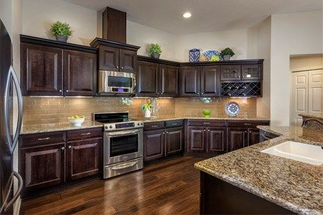 Gleaming floors and subway tile complement dark cabinets and stainless steel appliances. New homes in Alexandria Pointe built by KB Home. Deland, FL.