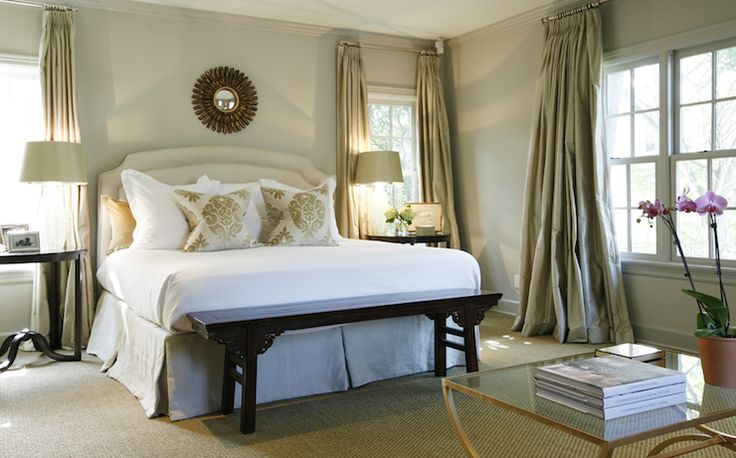 Ashley Goforth Designs    beautiful modern french romantic bedroom design with gorgeous blue & green bedroom! green silk pleated drapes, soft blue walls paint color, ivory headboard, green silk pillows, black asian altar bench, sisal rug, lamp and gold sunburst mirror.