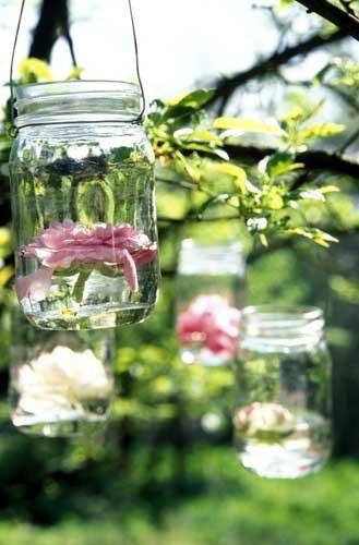 Hang mason jars with wire from trees with a flower floating in