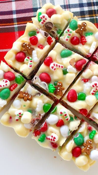 Recipe with video instructions: Packed with marshmallows, nuts and white chocolate, this might be the most addictive holiday treat ever. Ingredients: 800 grams white chocolate, 250 grams unsalted butter, 1/2 cup corn syrup, 3 teaspoons pure peppermint extract, 300 grams mini marshmallows, 1 1/4 cups Christmas-coloured candies (+ extra for topping), 1/2 cup macadamia nuts, Candy cane and gingerbread man icing decorations