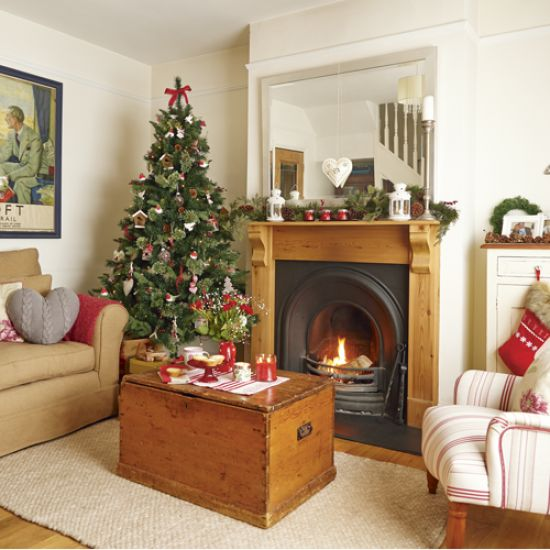 Country Christmas living room with neutral walls, wood flooring, neutral rug, white and red striped upholstered chair and Christmas tree